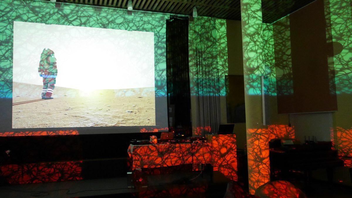 Astronaut auf Planet. Diese Abbildung zeigt das Bild, wie es später durch die Lichteffekte von der Lichtkünstlerin überlagert worden ist (siehe un- ten). Während der Performance war das Bild ohne überlagernde Effekte zu sehen gewesen.